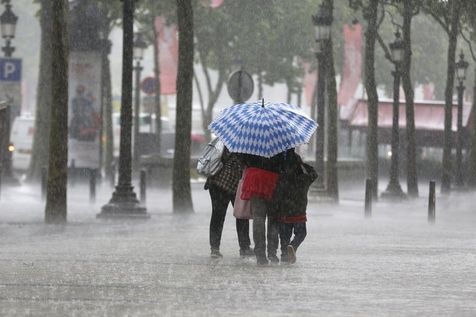 528338-des-personnes-affrontent-un-orage-le-17-juin-2013-sur-les-champs-elysees-a-paris