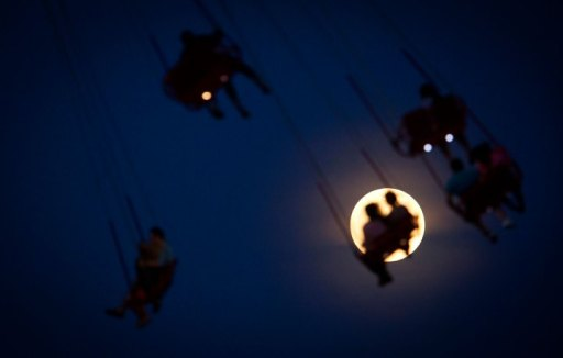People ride the Luna Park Swing Ride as the Super Moon rises on Coney Island