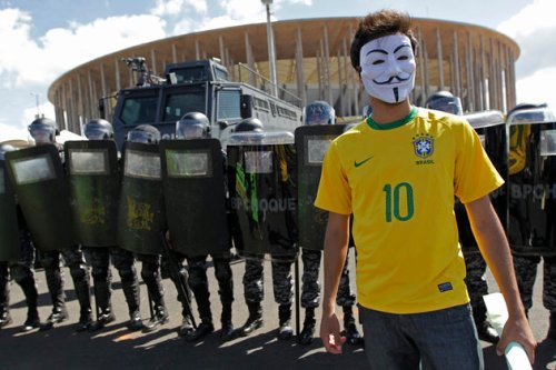 An activist demonstrates in front of riot police outside the Mane Garrincha National Stadium in Brasilia