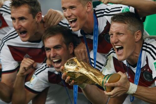 bastian-schweinsteiger-avec-la-coupe-du-monde-entoure-par-ses-coequipiers-le-13-juillet-2014-a-rio-archives